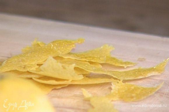 С двух оставшихся лимонов ножом для чистки овощей снять цедру длинными тонкими полосками.