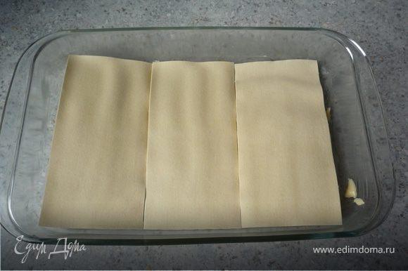 Разогореть духовку до 200°C. Форму для запекания смазать маслом. Выложить 3 листа лазаньи, сверху распределить 1/3 начинки.