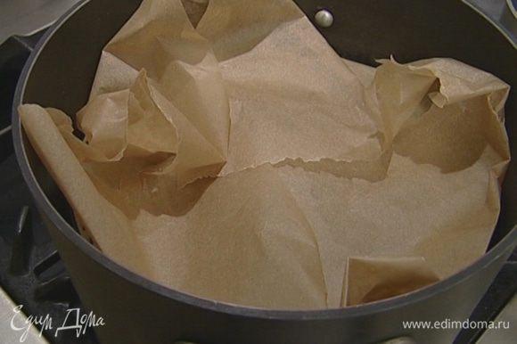 Накрыть кастрюлю бумагой для выпечки и прижать ее крышкой.