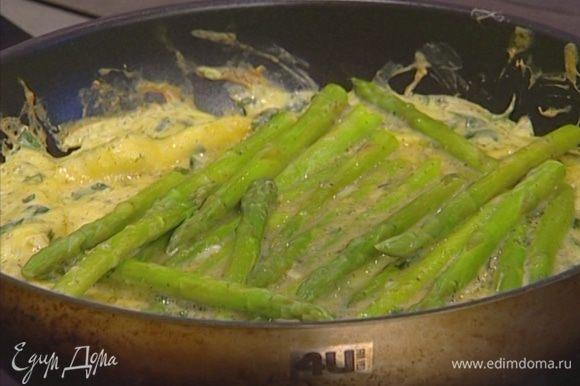 Сверху выложить спаржу, поперчить, посолить и отправить на пару минут в разогретую духовку. Если нет сковороды со съемной ручкой, духовку можно оставить открытой.