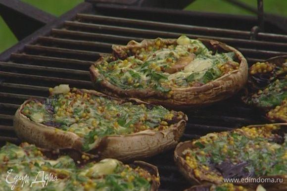 Положить грибы на гриль начинкой вверх и жарить 3–4 минуты.
