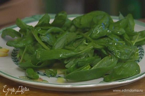 Шпинат вымыть, просушить, выложить на большое блюдо, сбрызнуть оливковым маслом и соком лимона, посолить и поперчить.