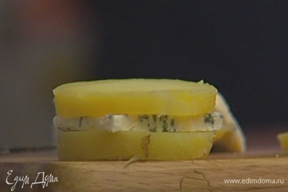 На каждый кружок картофеля положить кусочек сыра, сверху накрыть вторым кружком картофеля.
