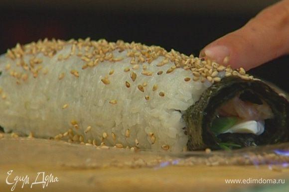 Свернуть ролл, ровно удерживая начинку, затем раскрутить коврик, удалить пленку и разрезать ролл на шесть частей.