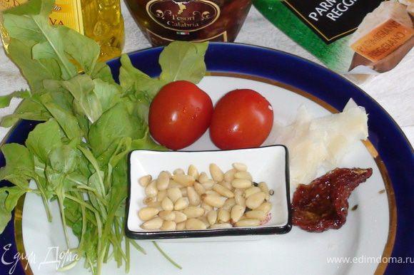 Руколу и помидорчики помыть, просушить; тонко нарезать пармезан. Подготовить кедровые орешки. Сушенный помидор порезать тонкими полосками.