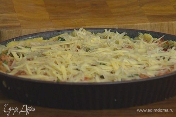 Выложить начинку в форму с тестом, присыпать натертым сыром и запекать в разогретой духовке 30–35 минут.