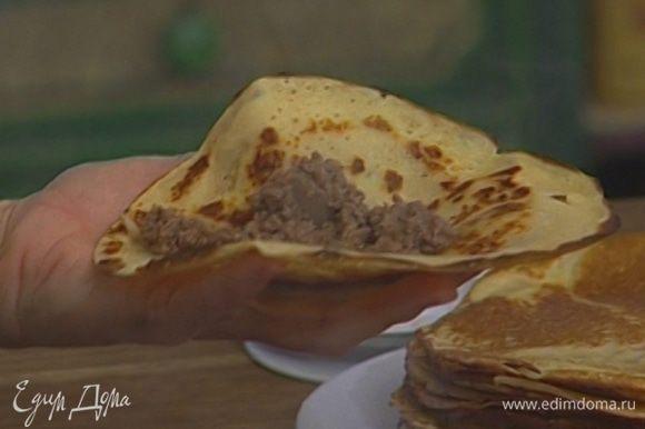 Выложить на каждый блин 2–3 ст. ложки фарша, свернуть блины в виде колбасок.