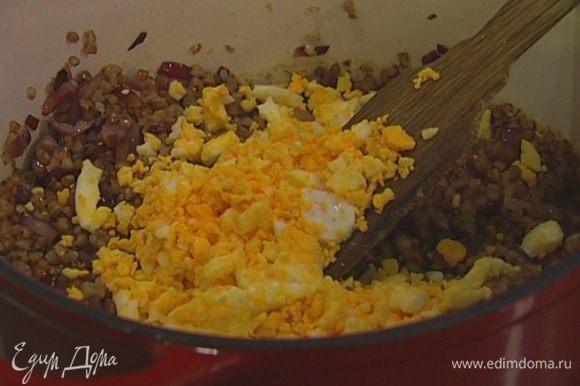 Добавить яйца, обжаренный и зеленый лук в гречку и перемешать.