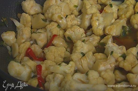 Добавить сахар, куркуму, влить рыбный и соевый соус, подогретый овощной бульон и тушить 10 минут, в конце всыпать кинзу.