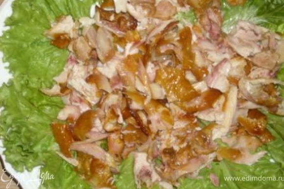 На блюдо выложить листья салата, затем курочку.