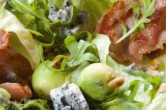 Листья салата выложить на большую тарелку, сверху посыпать кедровыми орехами, разложить бекон и сыр.