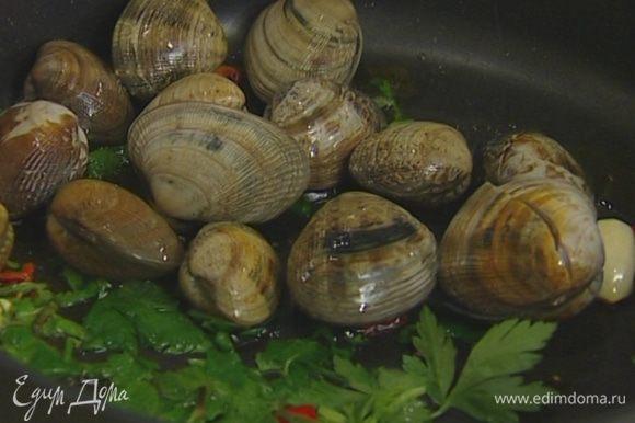 Добавить чили, половину петрушки, мидии и кальмаров, влить просекко, накрыть сковороду крышкой и готовить 3 минуты на сильном огне.