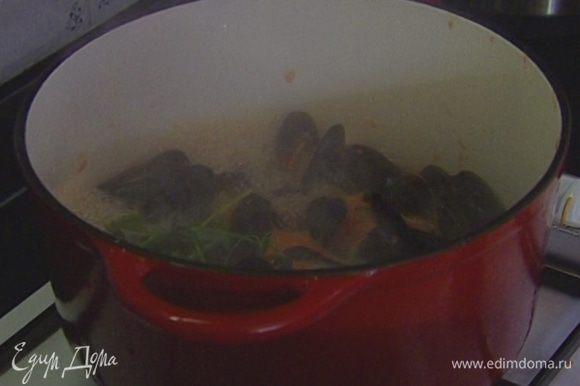 В тяжелой кастрюле большего размера разогреть 1 ст. ложку оливкового масла, выложить оставшиеся помидоры с соком, чеснок и петрушку. Добавить мидии, влить вино и 125 мл горячей кипяченой воды. Когда вода закипит, накрыть крышкой и готовить 5‒7 минут.