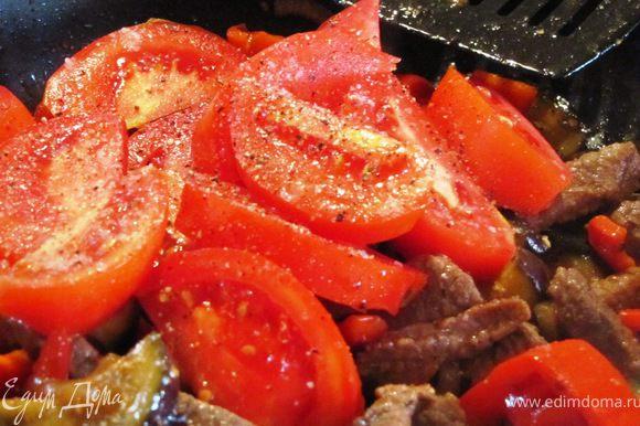 Через 3-5 минут добавляем нарезанный дольками помидор, дополнительно перчим, солим и перемешиваем.