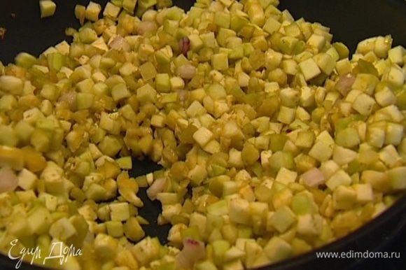 Разогреть в сковороде растительное масло и обжаривать баклажаны вместе с луком в течение 10 минут, затем посолить и поперчить.