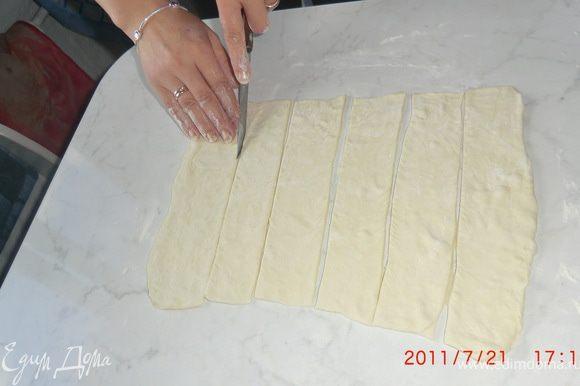 Тесто разморозить. Затем немного раскатать в одном направлении на смазанном маслом столе. Нарезать на полоски шириной 2-5 см.