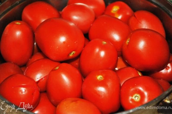 2 кг помидоров (выбрать помельче и потверже) вымыть, сделать надрезы, сложить в кастрюлю и залить кипятком. Накрыть крышкой и оставить на 20 мин.