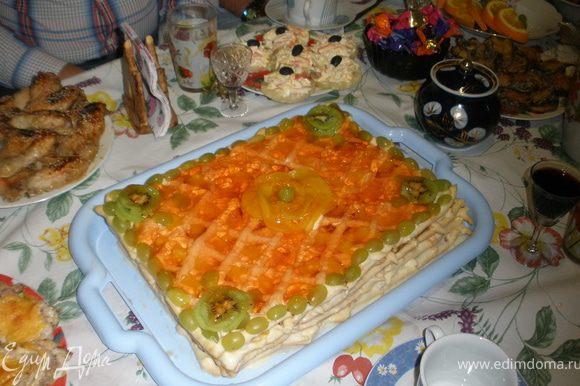 На блюдо для подачи положить первую решетку и в пустоты разложить кусочки фруктов на ваш выбор, подойдут любые: апельсин, банан, яблоки, виноград без косточки, смородина, вишня, персик. Сверху смазать кремом. Положить следующую решетку и так далее. Верх торта смазать кремом и поставить в холодильник, чтобы крем немного застыл. Затем верх торта украсить тонко нарезанными фруктами и залить прозрачным желе ( я прозрачный не нашла, взяла апельсиновый 2 пакета). Торт хранить в холодильнике, он должен пропитаться. И вот что у меня получилось! Прошу прощения за основное фото, сама сфотографировать не успела, это муж в последний момент на столе сфоткал.