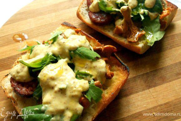 Чиабату нарезать поперек, сбрынуть оливковым маслом, подсушить на сухой сковороде, с двух сторон. На одну половину выложить колбасу, лисички, руколу, немного соуса, сбрызнуть маслом. Накрыть второй половиной и подавать!