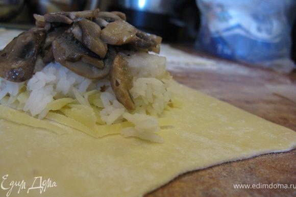 На каждую лепешку выложить порцию тертого сыра, на него - вареный рис, затем кусочек обжаренной рыбы и сверху грибы.