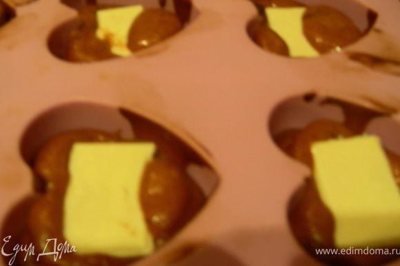 Затем кладем в каждый по кусочку батончика Марс или кусочку белого шоколада.