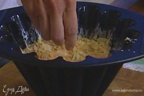 Форму для десерта смазать растительным маслом, выложить в нее лимонное мороженое, распределив его по стенкам и оставив в середине углубление, и немного присыпать печеньем с миндалем.