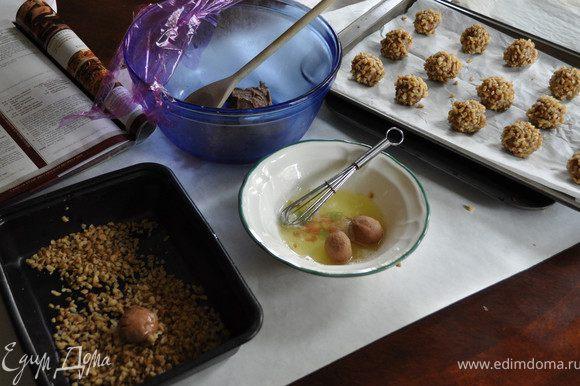 Белки взболтать,отложить.Орехи порубленные выложить в удобную посуду. Достать тесто,сделать небольшие шарики,окунать вначале в белки, а затем в орехи.Со всех сторон обкатать.