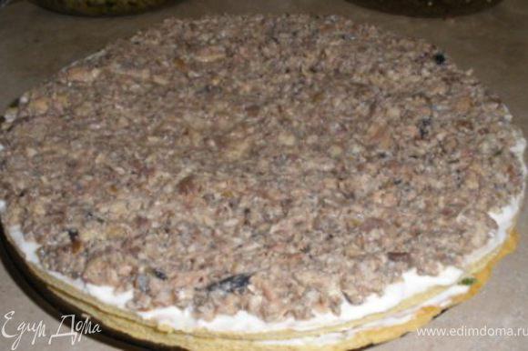 Укладывается пирог следующими слоями: 1-корж, смазывается плотно майонезом и высыпается половина нарезанных яиц с зеленым луком, все равномерно распределяется по коржу. 2-сверху ложится следующий корж, смазывается плотно майонезом и выкладывается равномерно вся рыбная начинка.