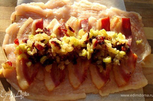 Куриные грудки поместить в целлофановый пакет и отбить молоточком с внутренней стороны,затем посолить и поперчить.Для первой начинки мелко нарезать лук и сельдерей и обжарить на растительном масле.Добавить тимьян(петрушку),клюкву и панировочные сухари.Посолить.Под отбитые грудки подстелить лист пергамента,по размеру грудки.На одну часть куриной грудки выложить ломтики прошутто,а затем начинку.С помощью пергамента плотно свернуть рулет и обернуть его пергаментом.Края грудки завернуть в рулет.
