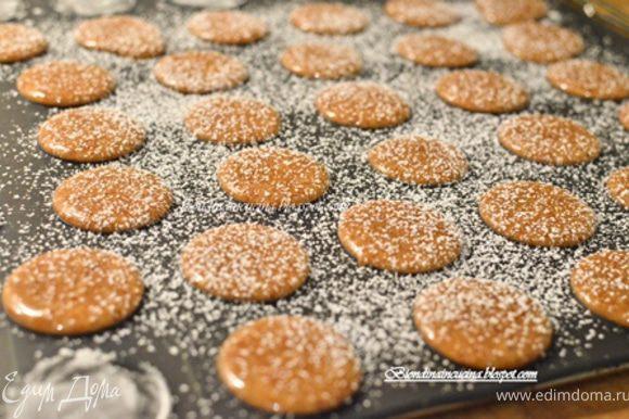 Затем взять кусочек пищевой пленки,положить сверху на macarons и придавить их слегка ладонью.Пленку убрать,посыпать их сахарной пудрой. перекладываем силиконовый коврик на решетку,все это вместе ставим в духовку на 10-12 мин.