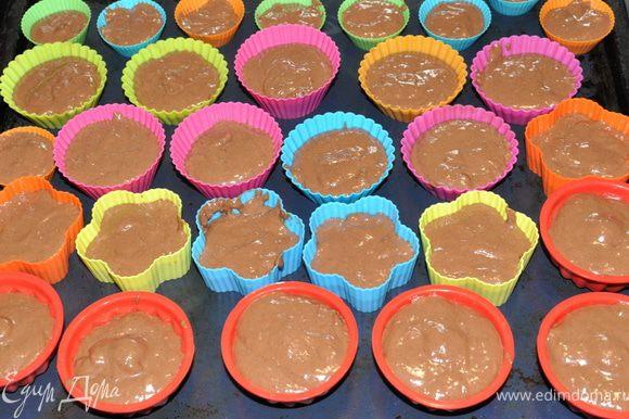Смазать формочки маслом (силиконовые не смазывать) и наполнить на две трети тестом.