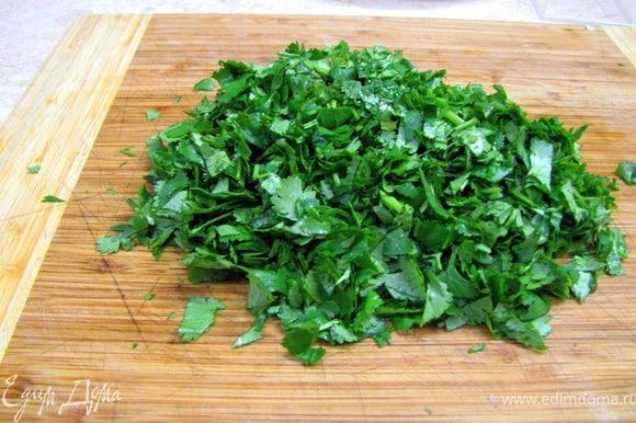 Возьмите кинзу и петрушку, оторвите или отрежьте стебли. Порубите зелень довольно мелко.
