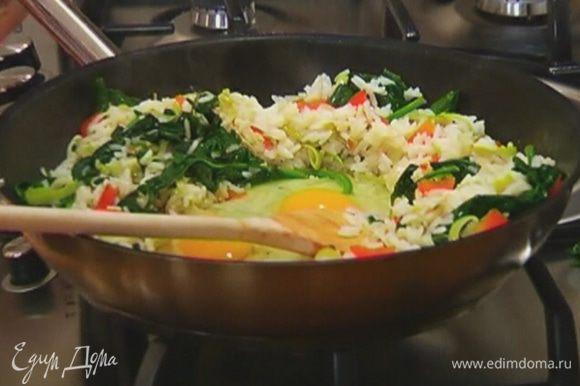 Отодвинуть рис с овощами к стенкам сковороды, в середину разбить яйца и, помешивая, обжарить их, затем перемешать с рисом.