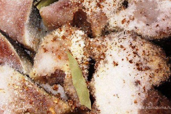 Тушки сельди помыть и порезать на 1.5 см кусочки. Сложить их в маленькую кастрюльку или мисочку. Лавровые листья поломать на 3-4 частицы и положить между кусочками рыбы. Посыпать сверху хмели-сунели, сухой чеснок, сахар и соль.