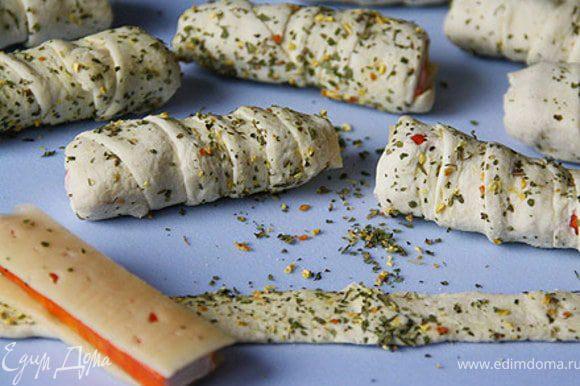 Из сыра нарезать на пластины по длине и ширине крабовых палочек. Крабовые палочки положить между 2-х полосок сыра и завернуть в полоски теста. Выпекать при 180 градусов 25 минут.