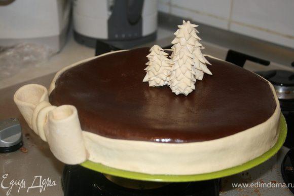 Раскатать шоколадную мастику, покрыть торт и украсить елочками и бантом. Если на мастике останется пудра смазать эти места водкой при помощи кулинарной кисти.