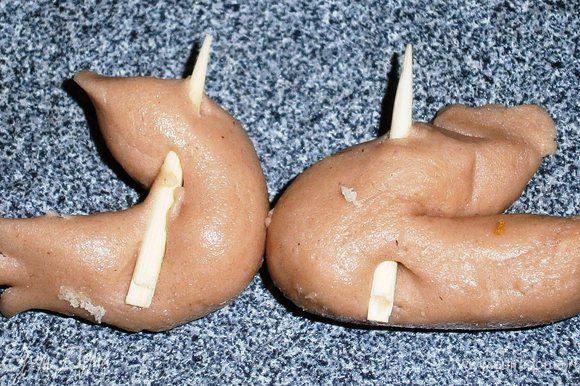 Далее берем оставшиеся зубочистки, ломаем пополам. Из мастики формируем 2 колбаски толщиной 1 см. Один конец каждой колбаски надрезать 2 раза, так , чтобы получилась лапа с 3 пальцами. Сложить колбаски их пополам. Воткнуть зубочистки: в первую лапку воткните зубочистку, кода пальцы на лапе смотрят вправо, а на второй лапке, когда пальцы смотрят влево. Замените зубочистки-подпорки на лапки-зубочистки. Сделайте анологично задние лапы, но пусть они будут чуть толще.