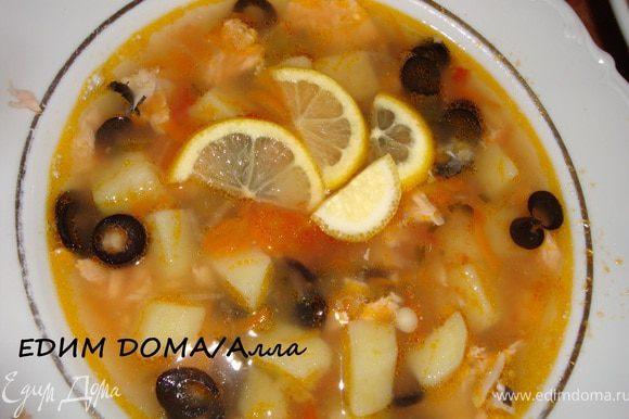 Раскладываем рыбку по тарелкам, наливаем солянку, добавляем ломтики лимона и оливки (маслины). Приятного аппетита!