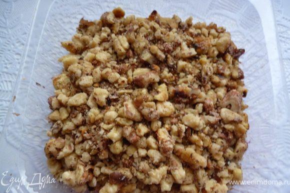 Орехи обжарить на сковороде и измельчить их скалкой.