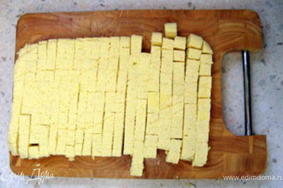 Через час достать из формы запеканку, перевернув её, отделить от бумаги и нарезать на мелкие кубики. Выложить кубики в супницу или тарелки и залить горячим бульоном.