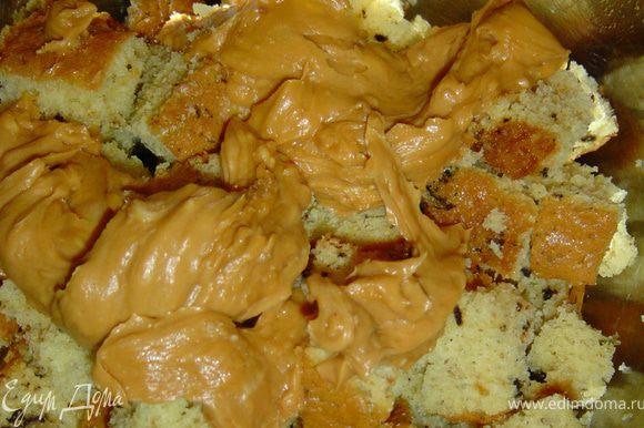 Готовим крем под мастику, взбиваем размягченное сливочное масло с вареной сгущенкой. Маленький корж нарезаем небольшими кусочками и соединяем с 1/3 масляного крема.