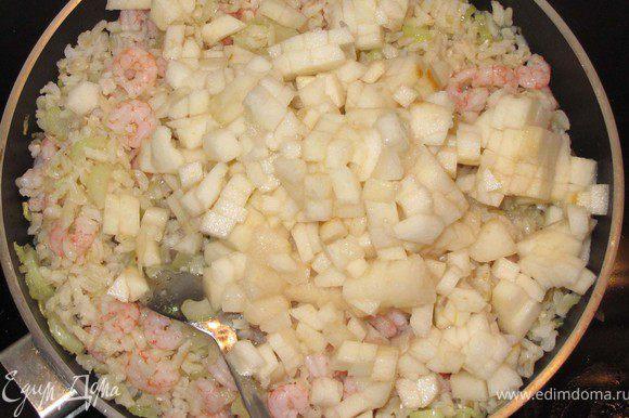 Отваренные креветки и рис выложите в сковороду, добавьте грушу, всё перемешайте и подержите на плите еще пару минут.