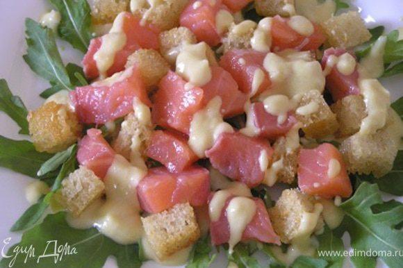 Выложить крутоны и нарезанную небольшими кубиками семгу на листья рукколы, полить соусом.