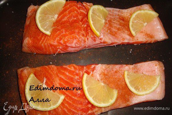 Лимон порезать тоненькими полукружочками и разложить по рыбе...