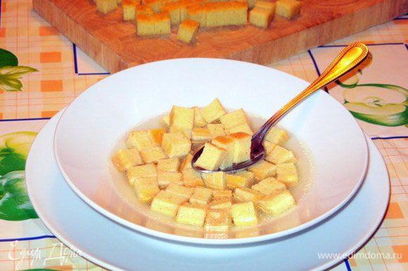 Залить кубики в тарелках горячим бульоном и дать постоять пару минут, чтобы они пропитались бульоном.