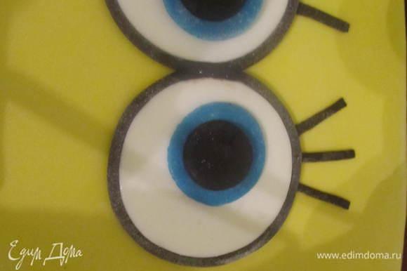 Глаза обвести жгутиком из черной мастики. В середину каждого глаза вырезать из голубой мастики кружок поменьше, его также подчеркнуть жгутиком, сделать зрачки, реснички.
