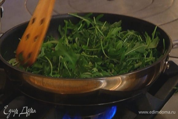 Не измельчая руколу, добавить ее в сковороду, перемешать с луком и прогревать все вместе около минуты, затем снять с огня.