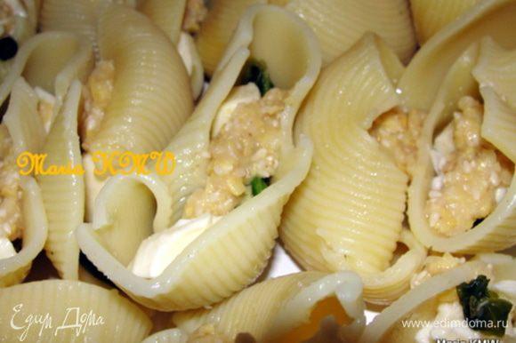 И теперь добавляем в каждую раковинку-лумакони по-кусочку моцареллы, на сыр выкладываем по 1 ч.л. хумуса, несколько листоков шпината, пару кусочков рубленного чеснока. Прикрываем еще одним кусочком моцареллы.