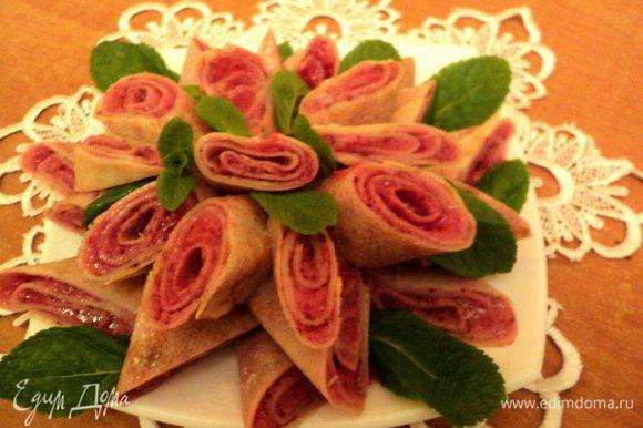 Готовые блинчики разрезать под углом, выложить на блюдо, присыпать сахарной пудрой через ситечко. Украсить листиками мяты и ягодками красной смородины. Приятного аппетита!