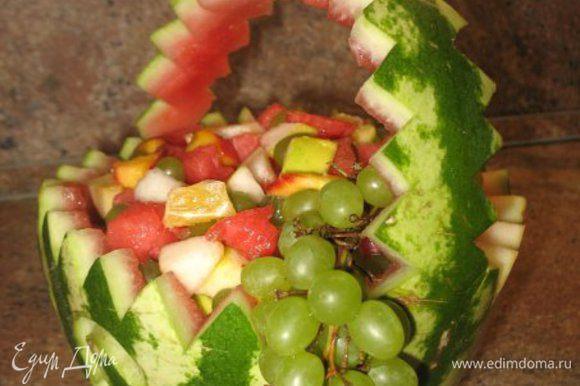 Корзинку из арбуза наполняем порезанными на кубки: арбуз,персик,яблоко ,груша,апельсин,виноград. Всё поливаем чуть мёдом и перемешиваем!!!)